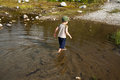 Boy wading in water small shallow on sunny day Royalty Free Stock Image