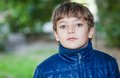 Boy walking in autumn time very serious outdoor weared blue jacket head and shoulders shot blank expression on the face Stock Images