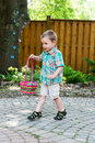 Boy walking with an easter basket a cute holds a colorful full of eggs he has found during egg hunt in a garden in the spring part Stock Photography