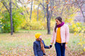 Boy walking with his mother in autumn park Royalty Free Stock Photo