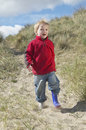 Boy walking on sand at beach full length of happy young Stock Photos