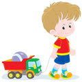 Boy walking with toys little pulling a toy truck a ball Stock Photos