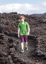 Boy walking in volcanic area on stones natural parc lanzarote Royalty Free Stock Image