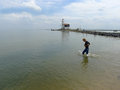 Boy walking in water front of lighthouse marken Royalty Free Stock Photos