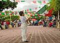 Boy waving mexican flag young in white clothes standing in village square of mexico during independence day celebration Stock Photo