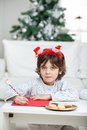 Boy wearing headband writing letter to santa claus portrait of at home Royalty Free Stock Photo
