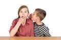 Boy whispering something to his astonished sister with eyes wide opened isolated on white half length studio shot background Royalty Free Stock Photo