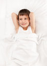 Boy in white bed lying on Royalty Free Stock Images