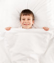 Boy in white bed lying on Stock Images