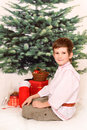 The boy in white shirt against fir tree sits christmas with presents Royalty Free Stock Photo