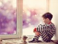 Boy in winter window cute little sitting on the windowsill the Stock Images