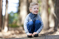 Boy in the woods positive smiling sitting at log Royalty Free Stock Photo