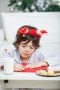 Boy writing letter to santa claus with milk and biscuits at home Stock Photo