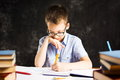 Boy writing in notebook on the desk covered in books Royalty Free Stock Photo