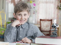 Boy of years learns house lessons smiling with school books on the table Stock Photography