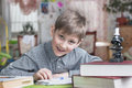 Boy of years learns house lessons smiling with school books on the table Royalty Free Stock Photos