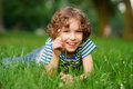 The boy of 8-9 years lies in a dense green grass. Royalty Free Stock Photo