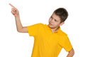 Boy in yellow shirt shows her finger to the side a young on white background Stock Photos