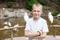 Boy in a zoo on background of birds Royalty Free Stock Photo