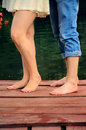 Boyfriend anf girlfrien feet standing no shoes on the pierce near lake Royalty Free Stock Photos