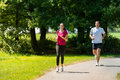 Boyfriend and girlfriend running a race outdoors caucasian in sunny park Stock Photo