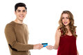 Boyfriend handing over the credit card to his girl handsome guy giving girlfriend for shopping Stock Photography