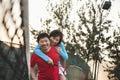 Boyfriend holding his girlfriend next to the tennis net Royalty Free Stock Photo