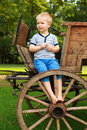 Boyhood memories old fashioned little boy sitting at a vintage wooden carriage Stock Photography