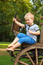 Boyhood memories old fashioned little boy sitting at a vintage wooden carriage Royalty Free Stock Photo