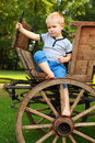 Boyhood memories old fashioned little boy sitting at a vintage wooden carriage Royalty Free Stock Images