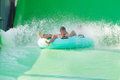 Boys in aquapark family on water slide at Stock Images