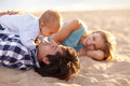 The boys bonding beautiful family of three lying happily on beach together for some time Stock Images