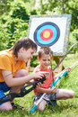 Boys with bows near sport aim in sunny summer day Stock Photography