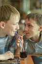Boys drinking coke two in cafe together Royalty Free Stock Image