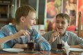 Boys drinking coke two cute in cafe Stock Images