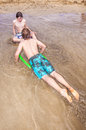 Boys enjoy surfing with a boogie board Royalty Free Stock Photo