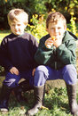 Boys in garden sitting after playing a autumn Royalty Free Stock Images