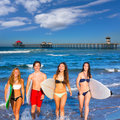 Boys and girls teen surfers coming out from the beach huntington california Stock Photography