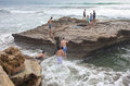 Boys and girls on the tidepool rock climb up onto Royalty Free Stock Photo