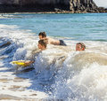 Boys have fun surfing with their boogie boards three in the ocean Stock Image