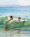 Boys have fun with their boogie boards two in the ocean Stock Photo