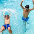 Boys having great time in pool portrait of two splashing water together Royalty Free Stock Photos
