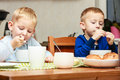 Boys kids children eating corn flakes breakfast meal at the table two blond brothers morning home Royalty Free Stock Photo