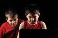 Boys at laptop in red sitting against dark background Royalty Free Stock Photo