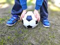Boys legs and ball holding hands on green grass. Royalty Free Stock Photo
