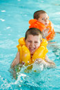 Boys in life jacket learning to swim the swimming pool Stock Image