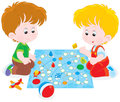 Boys playing with a boardgame children play board game on the floor Royalty Free Stock Photo