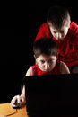 Boys playing computer game in darkness Stock Photography