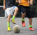 Boys playing footbal two teenage with colourful trainers tackling during a game of football on concrete Royalty Free Stock Photography