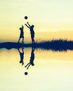 boys playing football at sunset with water reflection. silhouett Royalty Free Stock Photo